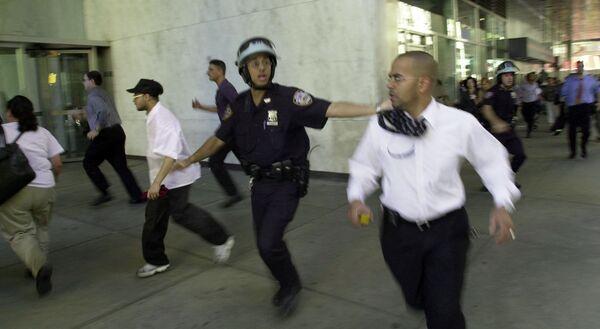 La folla in fuga durante il crollo di una delle torri del World Trade Center, dopo che i due aerei si sono schiantati contro gli edifici. - Sputnik Italia