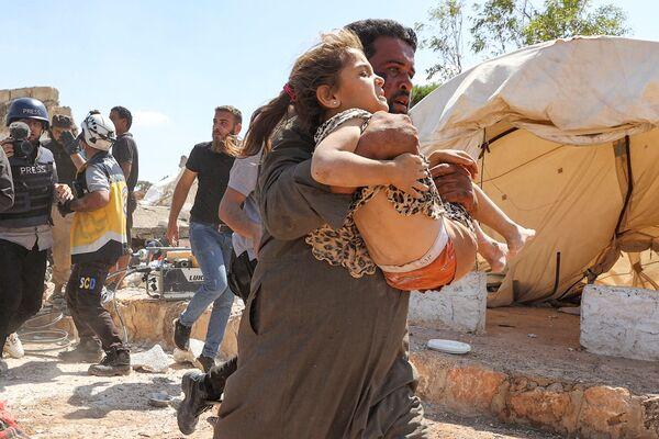 Un uomo porta via una ragazza ferita durante i bombardamenti aerei in un campo per sfollati siriani vicino alla città di Kafraya, nel nord della provincia siriana di Idlib, il 7 settembre 2021. - Sputnik Italia