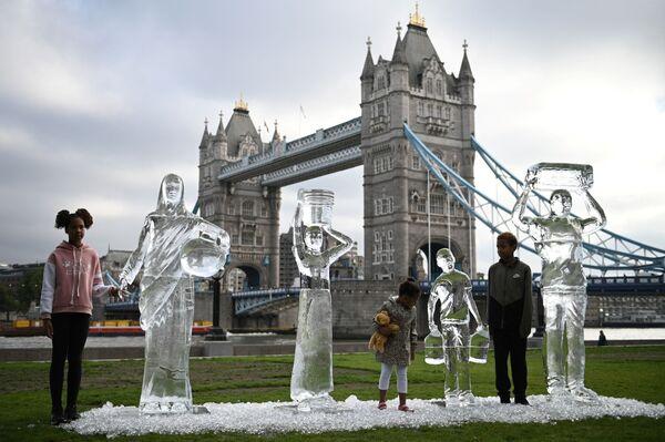 I bambini posano accanto a sculture di ghiaccio raffiguranti persone che raccolgono acqua dell'organizzazione benefica Water Aid, che vogliono sensibilizzare sulla scarsità delle riserve d'acqua e sulla minaccia rappresentata dai cambiamenti climatici, Londra. - Sputnik Italia