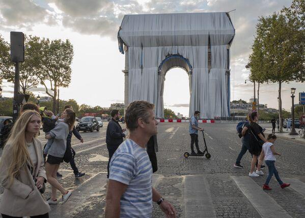 Uno dei principali monumenti di Parigi, L'Arco di Trionfo, è coperto di tessuto scintillante. L'arco è stato così trasformato in un'opera d'arte sviluppata dall'artista Christo Javacheff e da sua moglie Jeanne-Claude. L'artista è morto l'anno scorso e quindi, purtroppo, non ha visto realizzato il suo sogno. L'arco rimarrà avvolto fino al 3 ottobre. - Sputnik Italia