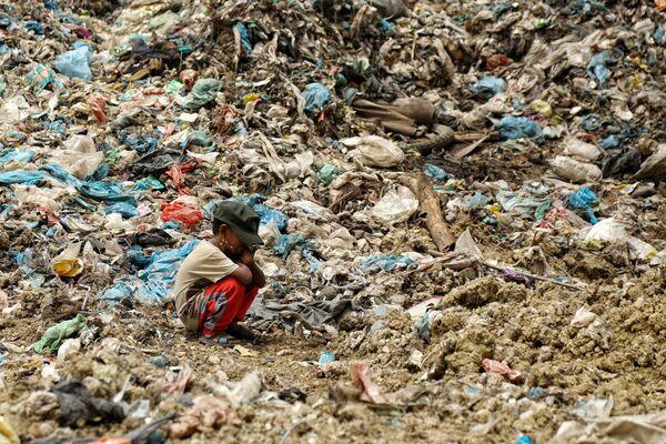 Il figlio di un netturbino riposa, mentre suo padre cerca oggetti che possono essere rivenduti, Lhokseumawe, Indonesia. - Sputnik Italia