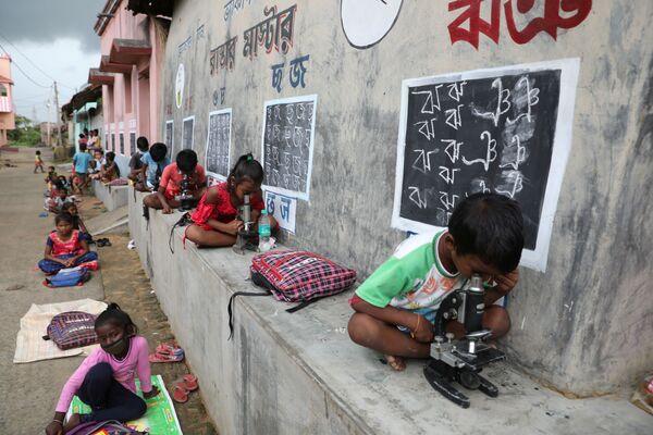 I bambini usano i microscopi, mentre frequentano una classe all'aperto, vicino alle case con le pareti convertite in lavagne, in seguito alla chiusura delle loro scuole a causa della pandemia di coronavirus, India. - Sputnik Italia