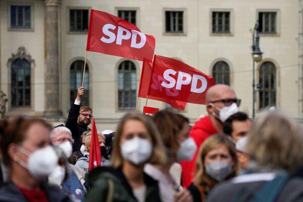 La folla sventola le bandiere del Partito socialdemocratico tedesco durante un evento per le elezioni federali, che si terranno il 26 settembre a Berlino. - Sputnik Italia