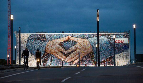 Il gigantesco striscione elettorale, raffigurante il famoso gesto delle mani a rombo della cancelliera tedesca Angela Merkel, apparso nel cantiere di un hotel a Berlino. - Sputnik Italia