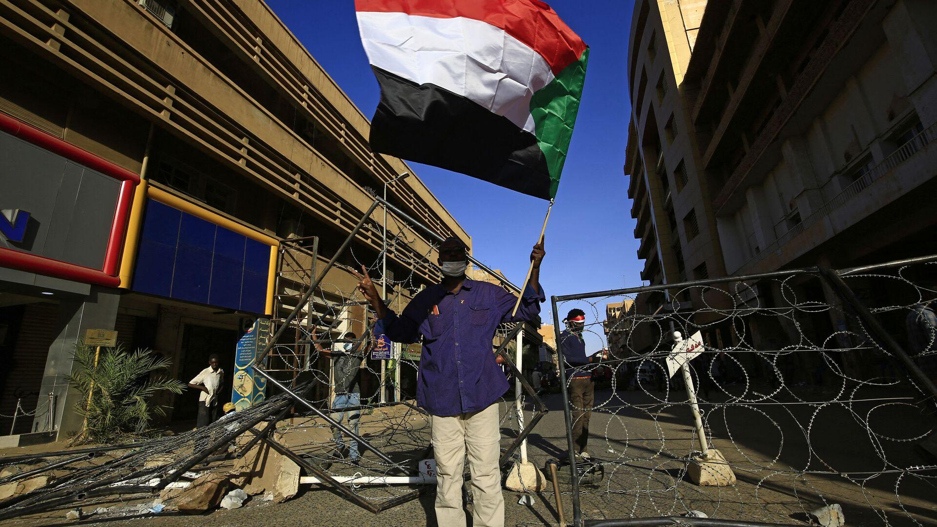 Un sudanese con la bandiera del proprio Paese a Khartoum - Sputnik Italia, 1920, 21.09.2021