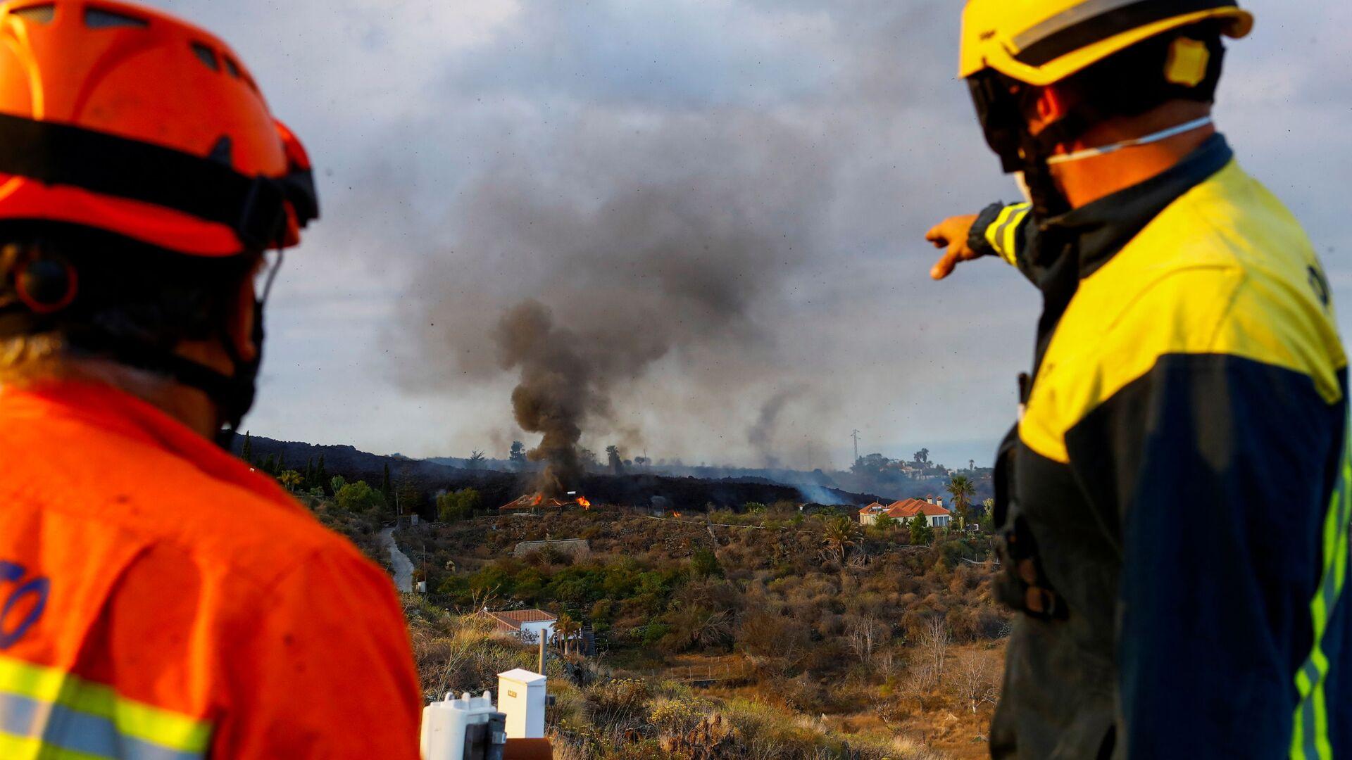 Сотрудник гражданской обороны и пожарный наблюдают, как горит дом из-за лавы в результате извержения вулкана в национальном парке Кумбре-Вьеха, в жилом районе на канарском острове Ла-Пальма - Sputnik Italia, 1920, 27.09.2021