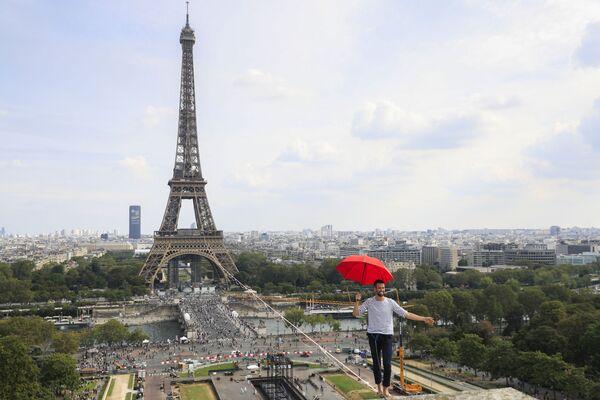 L'equilibrista, il 27enne Nathan Paulin, ha attraversato il fiume dalla Tour Eiffel al teatro Chaillot: ha camminato lentamente a piedi nudi sulla corda tesa fermandosi di tanto in tanto per riprendere la concentrazione: si sedeva, sdraiava ad un certo punto si è anche appeso alla corda, lasciandosi cadere nel vuoto.  - Sputnik Italia