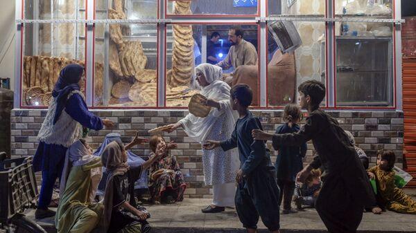 Женщина раздает хлеб нуждающимся детям перед пекарней в Кабуле - Sputnik Italia