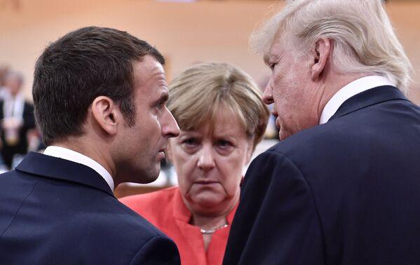 Il presidente degli Stati Uniti Donald Trump, il presidente francese Emmanuel Macron e la cancelliera tedesca Angela Merkel chiacchierano all'inizio della prima sessione di lavoro della riunione del G20 ad Amburgo, Germania - 7 luglio 2017. - Sputnik Italia
