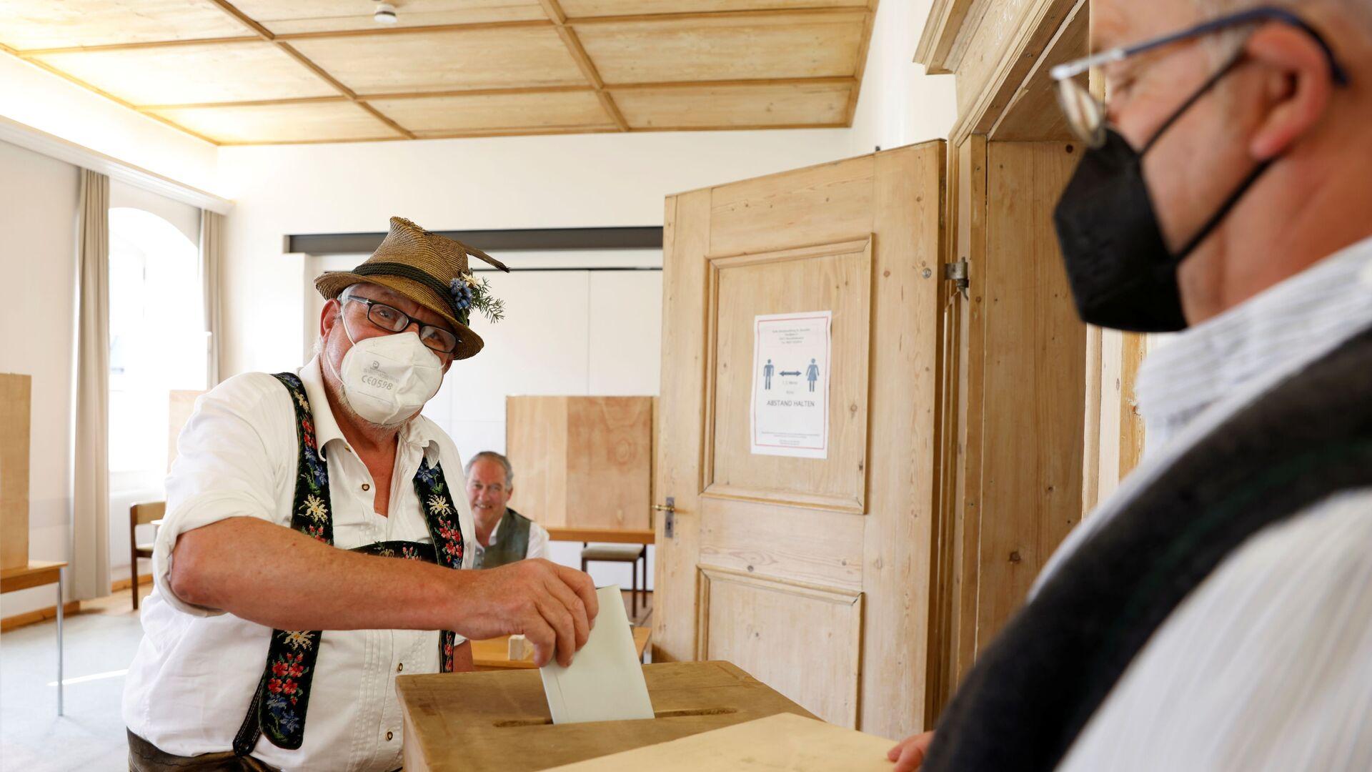 Мужчина в традиционном баварском костюме голосует в Бенедиктбойерне, Германия - Sputnik Italia, 1920, 29.09.2021