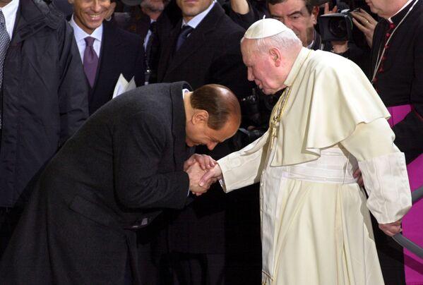 L'ex premier Silvio Berlusconi si inchina per salutare Papa Giovanni Paolo II dopo il suo arrivo alla stazione ferroviaria di Santa Maria degli Angeli, ad Assisi - 24 gennaio 2002. - Sputnik Italia
