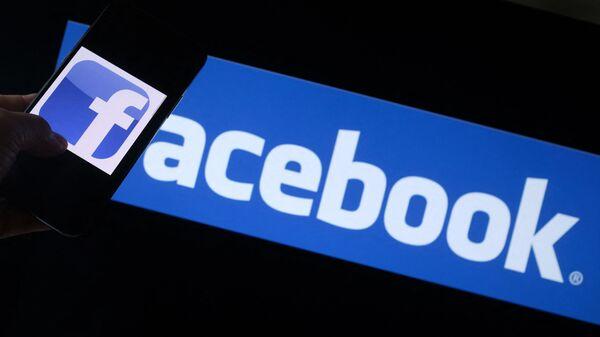 Логотип Facebook на смартфоне перед экраном компьютера в Лос-Анджелесе  - Sputnik Italia
