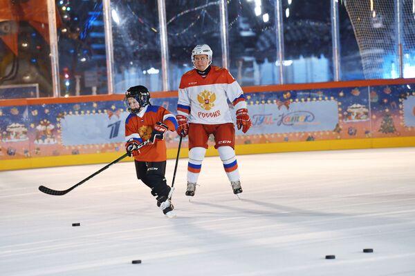 Vladimir Putin durante una sessione di allenamento di hockey con Dmitry Aschepkov, un partecipante di 9 anni alla campagna 'L'albero dei desideri' tutta russa del progetto di beneficenza 'Sogna con me', dalla regione di Chelyabinsk, presso la pista di pattinaggio GUM sulla Piazza Rossa di Mosca. - Sputnik Italia