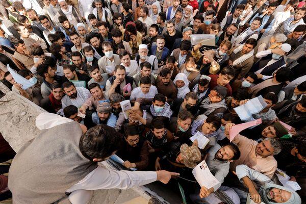 Afghani radunati davanti all'ufficio passaporti, dopo che i funzionari talebani (organizzazione terroristica illegale in Russia e molti altri Paesi) hanno annunciato il riavvio del rilascio dei passaporti ai cittadini, dopo mesi di ritardi, a Kabul, Afghanistan - 6 ottobre. - Sputnik Italia