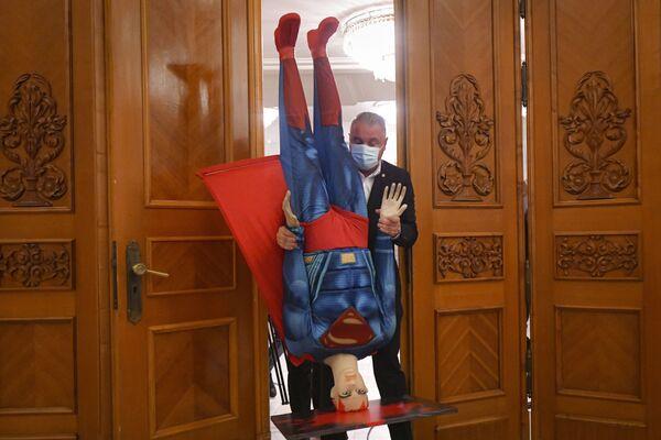 Un uomo con in mano un manichino di Superman prima del voto di sfiducia contro il governo del primo ministro rumeno Florin Citu nel parlamento rumeno a Bucarest, Romania - martedì 5 ottobre 2021. - Sputnik Italia