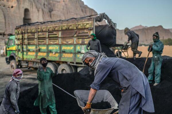 Lavoratori hazara si preparano a caricare il carbone su un camion vicino al luogo dove sorgeva la statua del Buddha Salsal, prima che venisse distrutta dai talebani nel marzo 2001, nella provincia di Bamiyan - 3 ottobre 2021. - Sputnik Italia