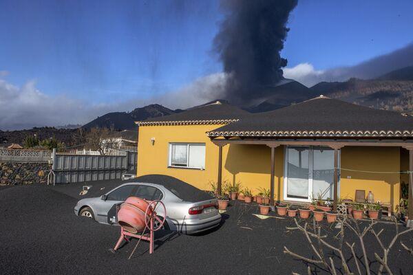 La cenere copre una casa, un'auto e un giardino, mentre sullo sfondo erutta il vulcano Cumbre Vieja sull'isola canaria di La Palma, Spagna - 4 ottobre 2021. - Sputnik Italia