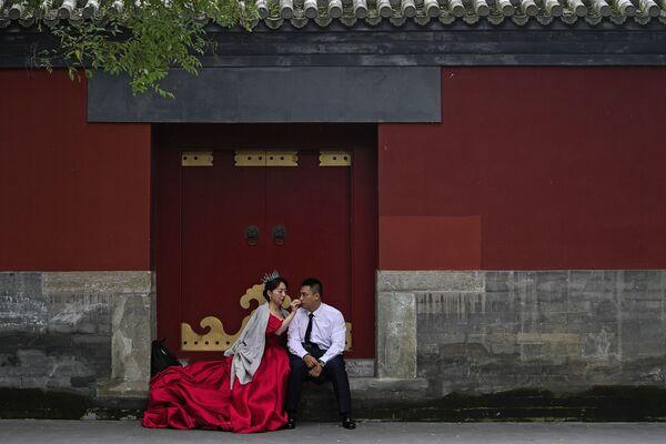 Una coppia di sposi in attesa del loro turno per scattare una foto pre-matrimoniale vicino alla Città Proibita, durante la settimana di festa nazionale a Pechino - domenica 3 ottobre 2021. - Sputnik Italia