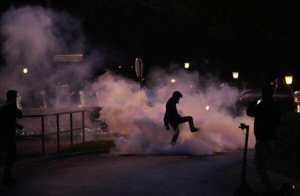 Un manifestante calpesta la bomboletta di un fumogeno durante una protesta contro l'obbligo vaccinale e contro le misure contro il coronavirus a Lubiana, in Slovenia - 5 ottobre 2021. - Sputnik Italia