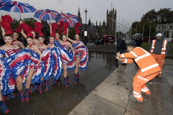 Alcuni operai scattano le foto alle ballerine del Moulin Rouge riparate dagli ombrelli a Londra - 4 novembre 2016. - Sputnik Italia