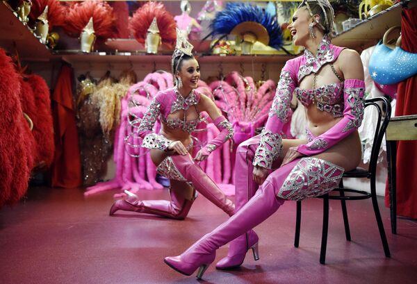 Le ballerine del cabaret Moulin Rouge si aggiustano gli stivali prima di uno spettacolo - 22 aprile 2014 a Parigi. - Sputnik Italia