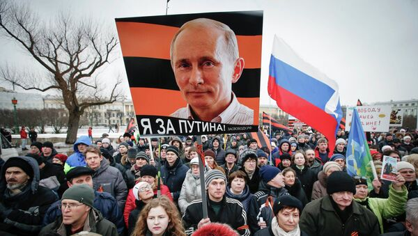 A photo of Russia's President Vladimir Putin is seen on a poster as people attend an Anti-Maidan rally to protest against the 2014 Kiev uprising, which ousted President Viktor Yanukovich, in St.Petersburg February 21, 2015. - Sputnik Italia
