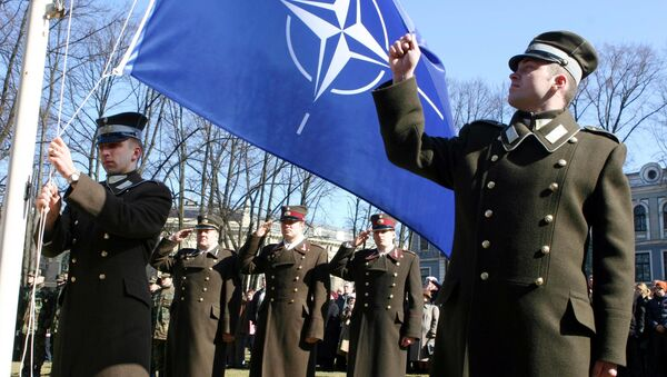 Latvian officers stand guard during the NATO flag rising ceremony in front of the Presidents castle in Riga - Sputnik Italia