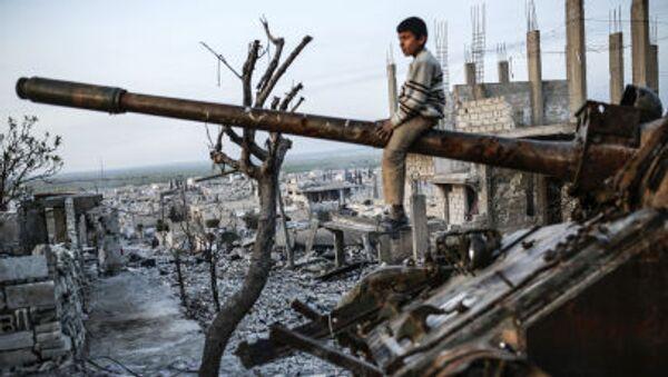 Un ragazzo kurdo sul carro armato destrutto nella città di Kobani, Siria - Sputnik Italia