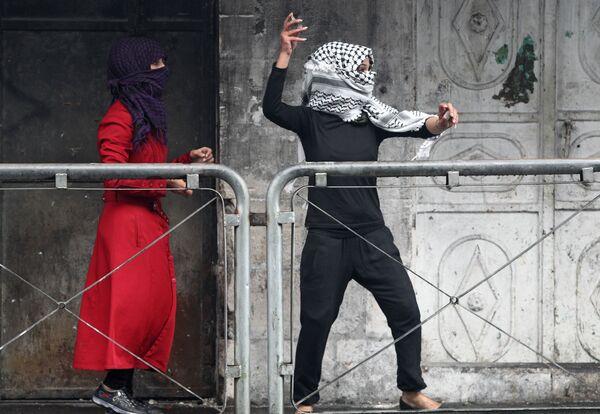 Due donne palestinese gettano sassi contro militari israeliani durante gli scontri in Cisgiordania. - Sputnik Italia