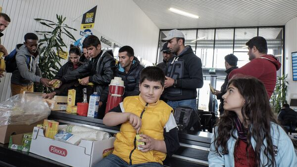 Refugees receive food upon arrival at the Tornio-Haaparanta bus station in Sweden after crossing the Finnish border on September 14, 2015 - Sputnik Italia
