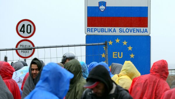 Migrants and refugees wait in the rain as they wait to enter Slovenia, at the Croatian-Slovenian border in Trnovec, on October 19, 2015. - Sputnik Italia