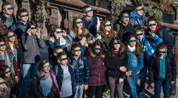 Monaco di Baviera, una scolaresca osserva l'eclisse indossando gli speciali occhialini. - Sputnik Italia
