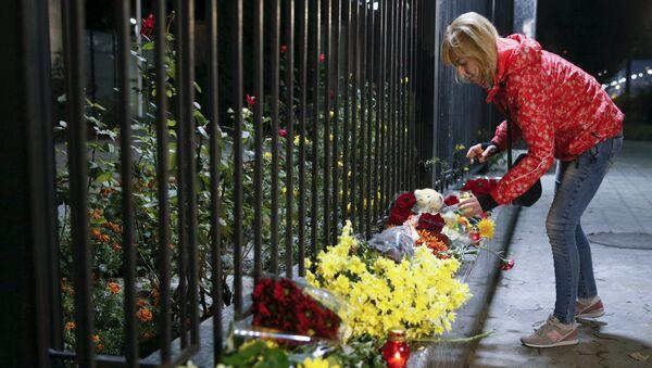 Una donna posa dei fiori in memoria delle vittime dell'attentato all'aereo russo nel SINAI - Sputnik Italia