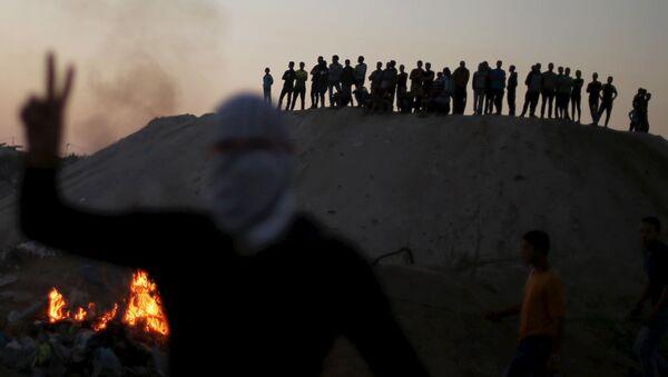 Палестинцы наблюдают за столкновениями с израильскими военными около города Газа в Палестинской автономии - Sputnik Italia