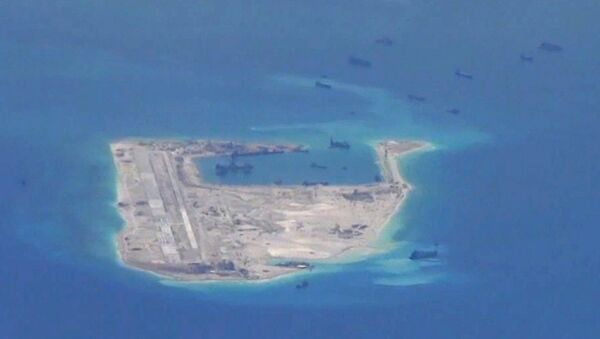 Chinese dredging vessels are purportedly seen in the waters around Fiery Cross Reef in the disputed Spratly Islands in the South China Sea in this still file image from video taken by a P-8A Poseidon surveillance aircraft provided by the United States Navy - Sputnik Italia