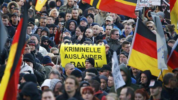 Le proteste di Pegida a Colonia, Germania, il 9 gennaio, 2016. Scritta sul cartello Stranieri clandestini fuori!. - Sputnik Italia