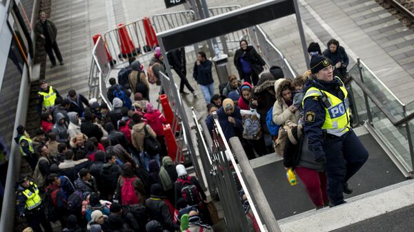 Police organize the line of refugees at on the stairway leading up from the trains arriving from Denmark at the Hyllie train station outside Malmo, Sweden, November 19, 2015. - Sputnik Italia