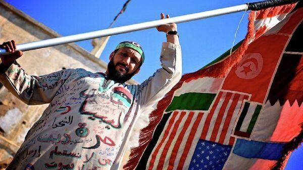 Un uomo tiene la bandiera di tutti i paesi coinvolti nella guerra civile in Libia - Sputnik Italia