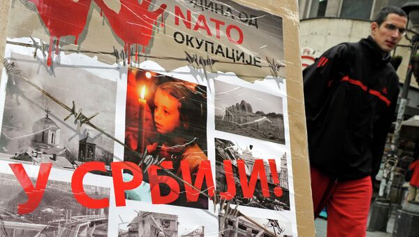 """A man walks past a poster with the reading """"Ten years of NATO occupation of Serbia"""", and displaying images from 1999 NATO air campaign against Serbia and Montenegro, in Belgrade on March 23, 2009.  - Sputnik Italia"""