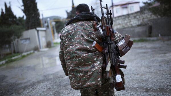 An ethnic Armenian fighter carries Kalashnikov machine guns to his comrade-in-arms at Martakert province in the separatist region of Nagorno-Karabakh, Azerbaijan, Monday, April 4, 2016 - Sputnik Italia