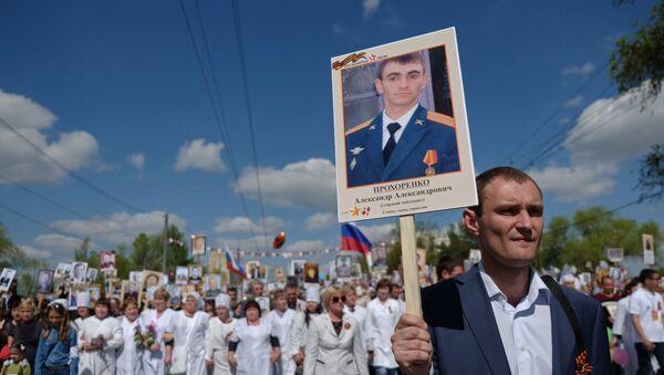 Un partecipante della manifestazione Bessmertny Polk ad Orenburg, Russia, porta la foto di Alexander Prokhorenko, il paracadutista acquisitore russo morto durante la liberazione di Palmira. - Sputnik Italia