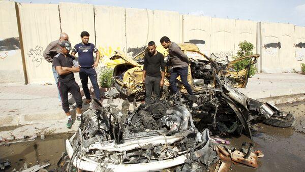 Iraqi men inspect the site of car bomb attack in Baghdad, Iraq (File) - Sputnik Italia