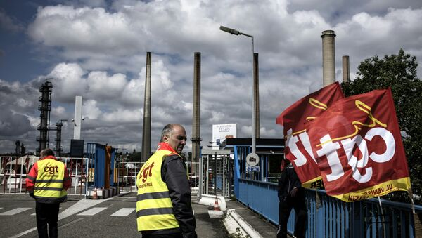 A worker stands next to French CGT union flags in front of the Total oil refinery of Feyzin, near Lyon, central-eastern France, on May 24, 2016, during a strike at the plant to protest against government labour reforms - Sputnik Italia