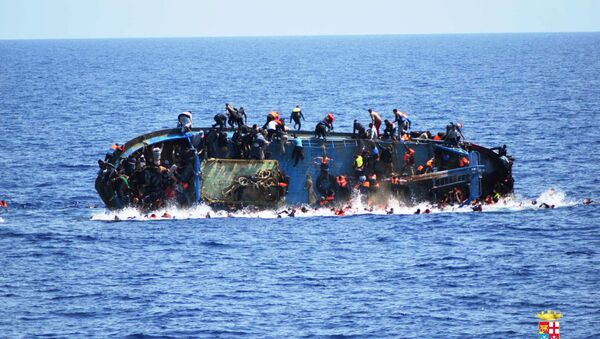 Migrants are seen on a capsizing boat before a rescue operation by Italian navy ships Bettica and Bergamini off the coast of Libya in this handout picture released by the Italian Marina Militare on May 25, 2016. - Sputnik Italia