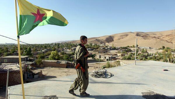 A Kurdistan Workers Party (PKK) fighters guards a post flying the PKK flag. File photo - Sputnik Italia