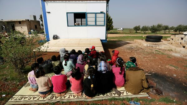 Children watch as volunteer teachers perform a puppet show inside a mobile educational caravan for children who do not have access to schools on the outskirts of the Syrian rebel-held town of Saraqib, Idlib province March 10, 2016 - Sputnik Italia