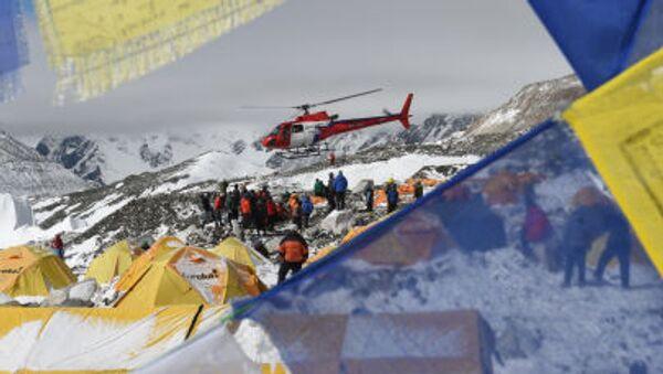 Поисковый вертолет, в обрамлении флагов с молитвами в Непале, забирает пострадавших после землетрясения из лагеря Everest Base Camp - Sputnik Italia