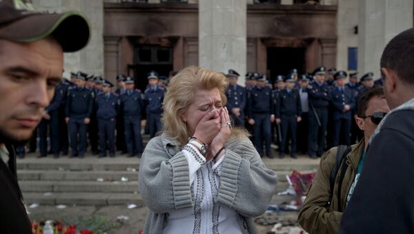 A woman cries back dropped by police troops guarding the burnt trade union building in Odessa, Ukraine, Saturday, May 3, 2014, where more than 30 people died trying to escape during clashes the day before - Sputnik Italia