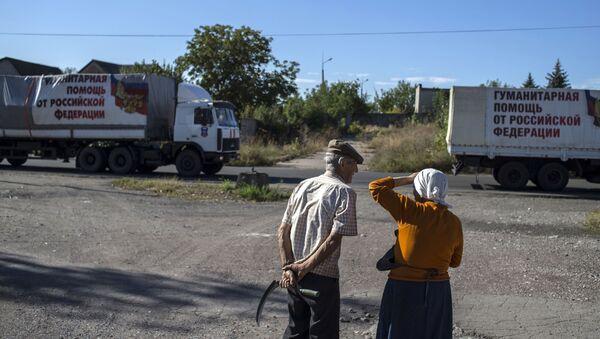 Due abitanti del Donbass guardano i camion che portano gli aiuti umanitari - Sputnik Italia