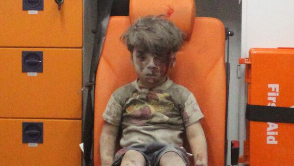 Five-year-old Omran Daqneesh, with bloodied face, sits inside an ambulance after he was rescued following an airstrike in the rebel-held al-Qaterji neighbourhood of Aleppo, Syria August 17, 2016 - Sputnik Italia